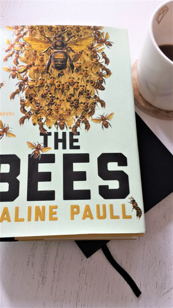 a book called The Bees, sitting on a coffee table.
