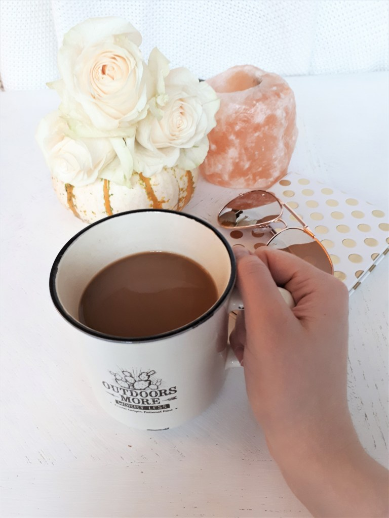 womans hand holds fresh mug of coffee mug, with fresh white roses and a white and orange pumpkin in the background