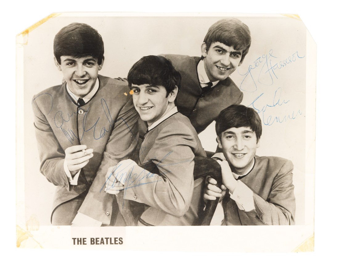 An 8-by-10-inch black-and-white publicity photograph of the Beatles, shot on March 24, 1964 by Dezo Hoffman and signed in blue pen by all four band members.