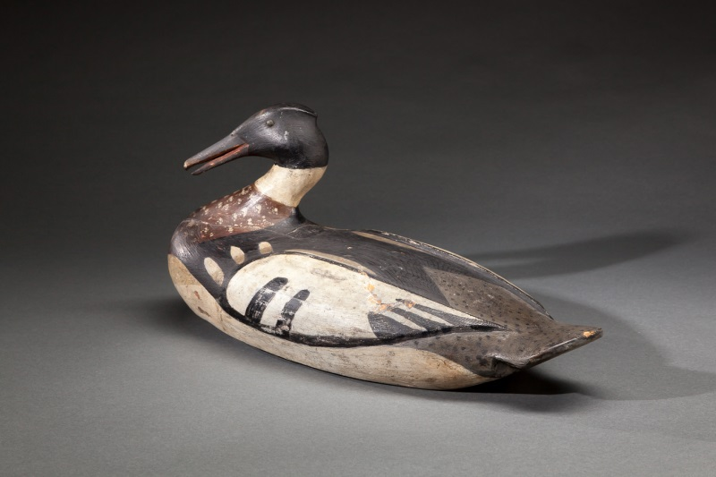 """A red-breasted merganser drake duck decoy, carved circa 1900 by Augustus """"Gus"""" Wilson. It had been described as the finest Wilson decoy ever offered at auction. Copley Fine Art Auctions sold it in July 2014 for $330,000, achieving an auction record for the artist."""