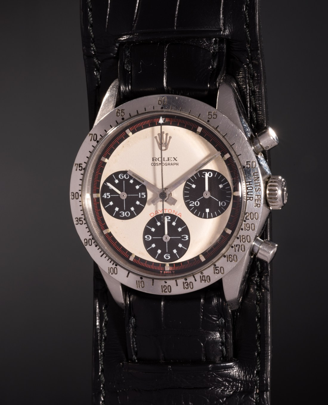 """A 1968 Rolex Daytona """"Paul Newman,"""" reference 6239 and owned by the late actor Paul Newman. Purchased for him by his wife, Joanne Woodward, she engraved the back of the case with the words, """"DRIVE CAREFULLY ME."""" Estimated in excess of $1 million, Phillips sold it in New York in October 2017 for $17.7 million, a world auction record for any wristwatch."""