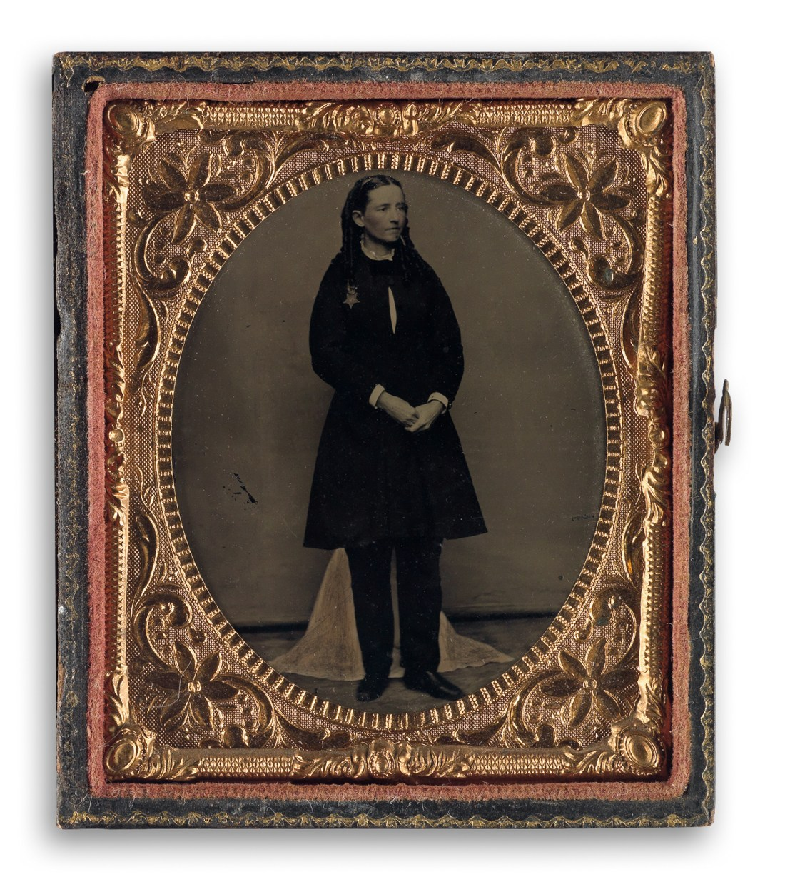 In this circa 1865 tintype, American physician Mary Edwards Walker wears her Medal of Honor. It appears on the upper left of her chest. She wears matching trousers under her black dress. She's depicted in three-quarter view, looking to the right, with her hands clasped.