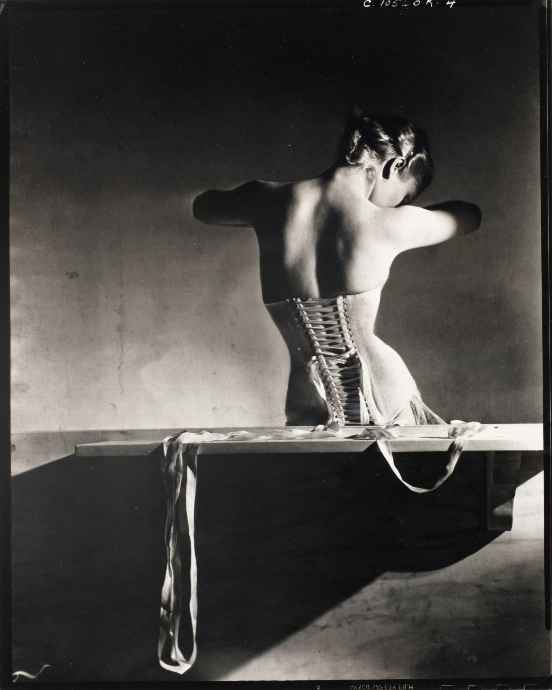 "Horst P. Horst's ""Mainbocher Corset"" is a lush black and white image of a young woman with her back to us. She seems to be sitting on some sort of bench. The ribbons of her white corset are unstrung and draped behind her and over the bench. She hides her face behind her shoulder like a dove tucks its beak into its wing."