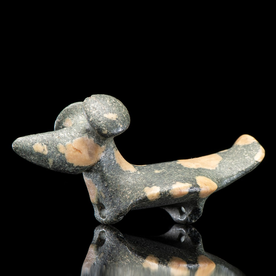 "A porphyry popeye fantail birdstone, created by the people of the Glacial Kame Culture sometime between 3,000 and 500 BCE in what is now DeKalb County, Indiana. It looks like a small dog, except it has two loops where the front and back feet should be. It is slate gray with pale cream-colored blobs of varying sizes across its body. It has two wide nailhead-like protuberances where its ears should be, but the protuberances are called ""eyes""."