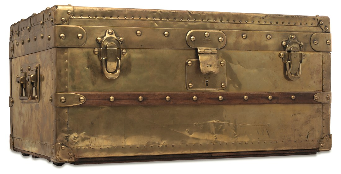 An 1888 Louis Vuitton brass Explorer trunk, shown in full, from the front. It is gold in color and features impressive buckles and locks.