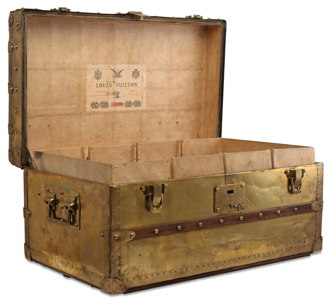 An 1888  brass Explorer trunk, shown in full, from the front, with its lid open to show the Louis Vuitton label. Though the paneling is made from brass, it has acquired a golden color over the years.