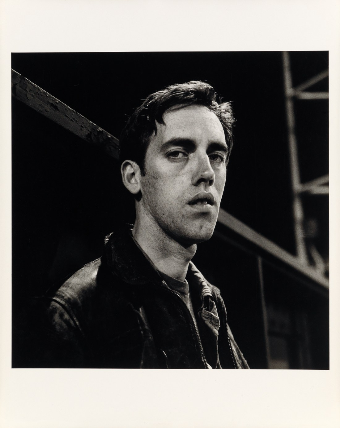 Peter Hujar's black and white print, David Wojnarowicz: Manhattan-Night (III), features his friend and mentee. David Wojnarowicz, looking directly at the camera with a moody, faintly sultry expression.