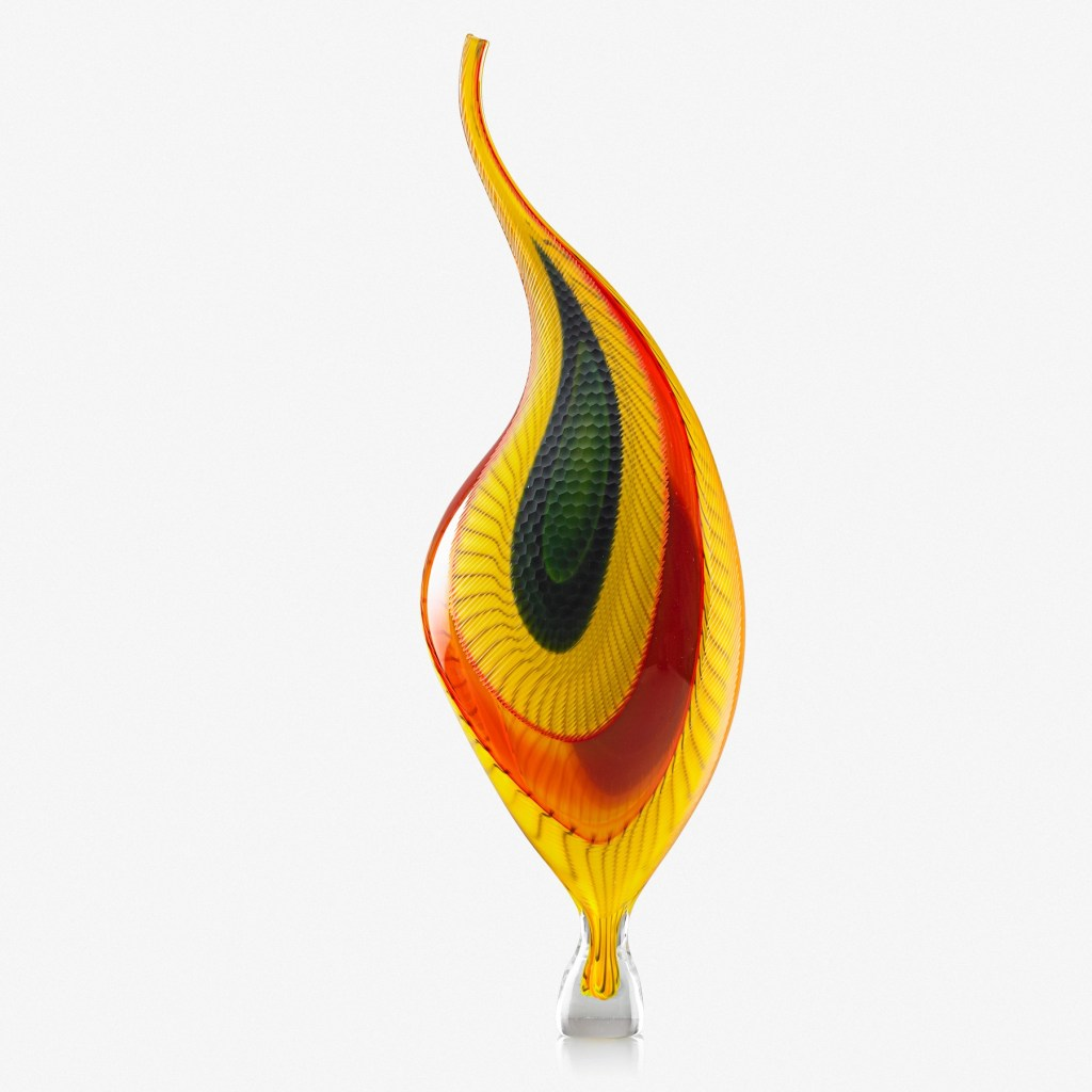 A Lino Tagliapietra Dinosaur, a glass sculpture created at Murano, Italy in 2008. It is flamelike and colored with bright yellow and red and hunter green. It's kind of teardrop-shaped.