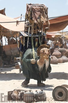 """One of the first creatures revealed as part of the new Star Wars menagerie was this desert merchant known as Bobbajo. The human performer shares only his legs with the alien, and the rest of his body extends up into the various cages being hauled on Bobbajo's back. (The actor can see through the mouth of the large amphibian-like creature in the middle cage.) """"He was envisaged as this sort of seller who would lumber his way to the market every day, selling these rather weird and strange creatures, which he had in the cages,"""" says Neal Scanlan, who headed the film's creature shop. """"He's very slow, he's very laid back."""" Judging by the drowsy look in his eyes, you wonder if Bobbajo may be hustling some herbal products, too."""