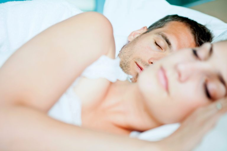 man and woman sleeping in a white bed