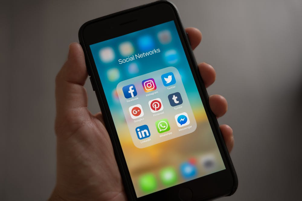 social media, hand holding cell phone with icons on screen