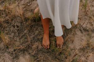 white dress, bare feet standing in dry grass and dirt
