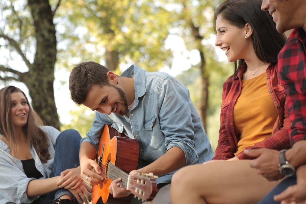 have fun in college, man playing guitar, girl smiling