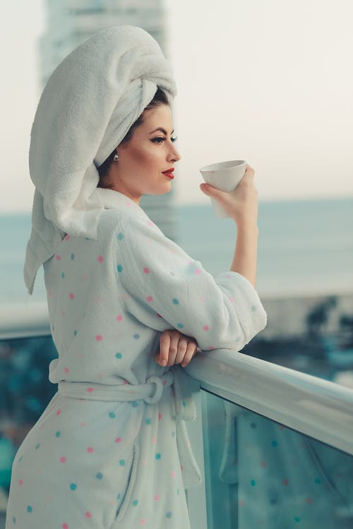 woman with towel on hand, coffee in hand, polkadot robe