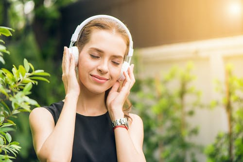 snap out of a bad mood, smiling woman listening to headphones