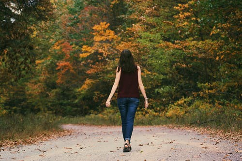 woman in jeans and burgundy shirt walking into woods