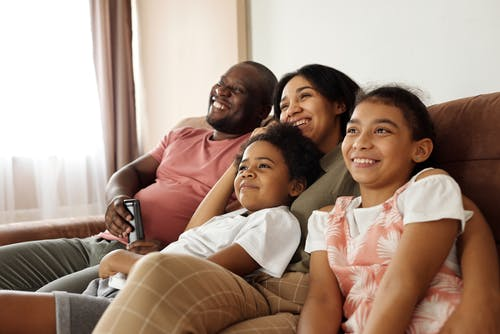 family snuggling on couch and smiling