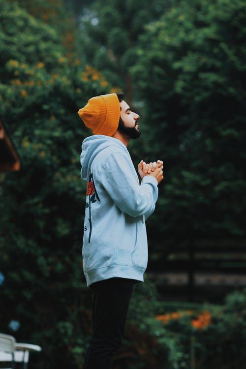 man wearing orange hat standing outdoors praying