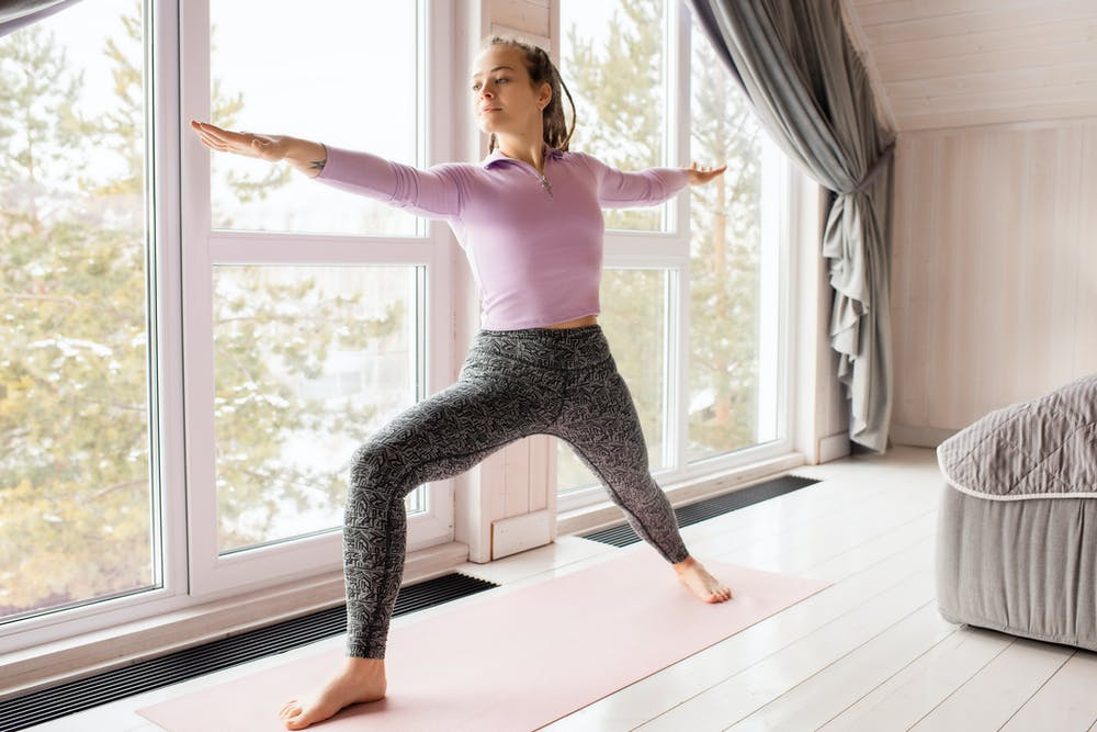 woman in pink top and gray leggings stretching by a window