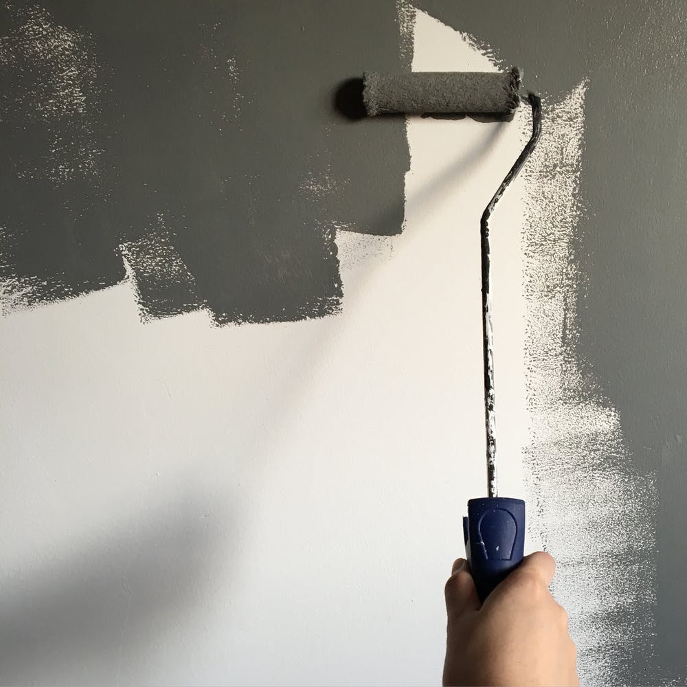 home interior, hand using roller to paint wall gray