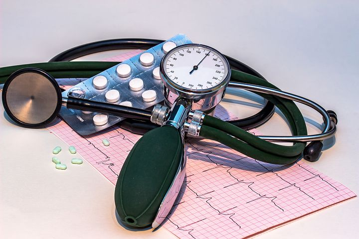 blood pressure, pressure guage and pack of pills sitting on paper chart