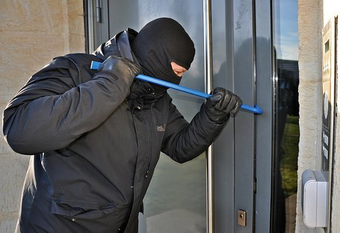 crime alert, man in black with ski mask prying door with blue metal bar