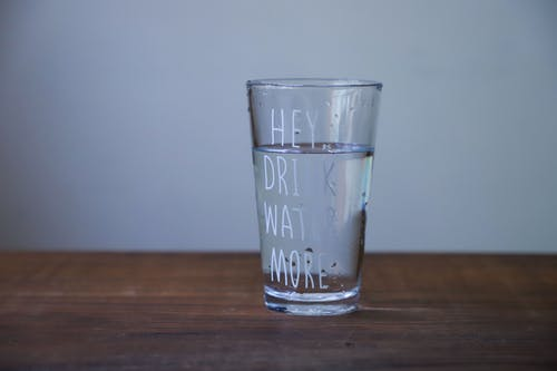 """glass of water, words on glass say """"hey, drink water more"""""""