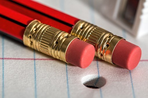 two red pencils with erasers lying on lined paper