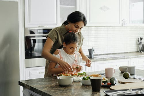 woman and girl preparing food together at kitchen island