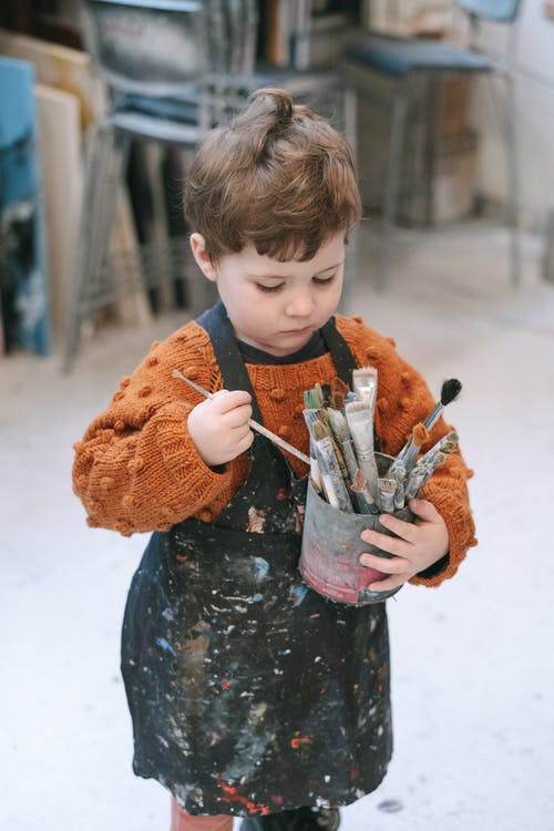 child in orange sweater, black apron, holding can of paintbrushes
