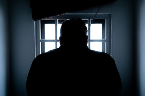 silhouette of man's back in front of window