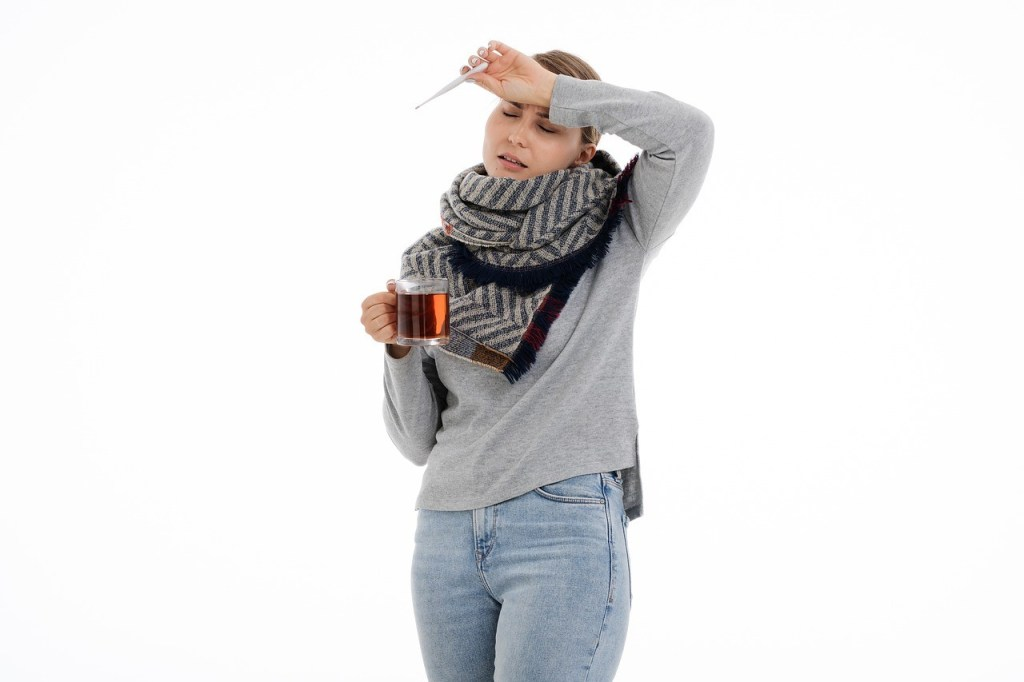 fever, woman in gray sweater and scarf, holding drink and thermometer with arm over forehead