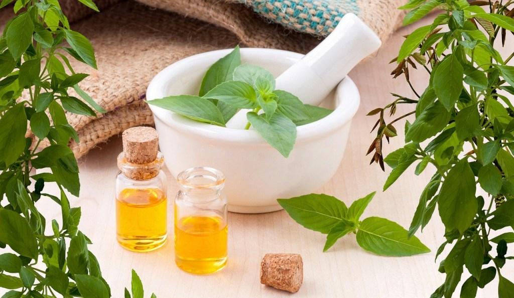 white bowl, green herbs, bottles of essential oil