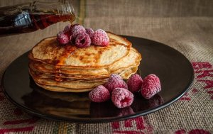 meal prep, pancakes with syrup and fresh berries on a plate