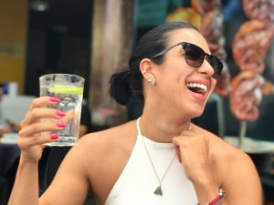feel more rested, woman wearing sunglasses and white dress smiling and holding glass of water with lemon in it