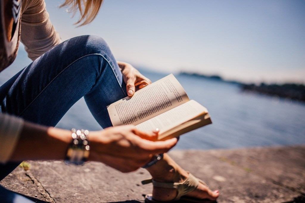 feel more rested, woman's leg and arms, hands holding a book, water in background
