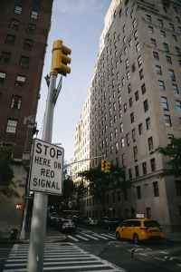 intersection safety tips, sign that says 'stop here on red', yellow car driving by