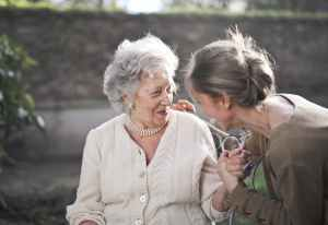 older woman in white sweater talking with younger woman, upswept hair, brown shirt