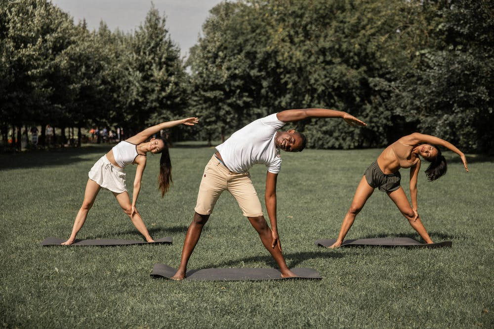 man and two women doing over-head side stretches outdoors