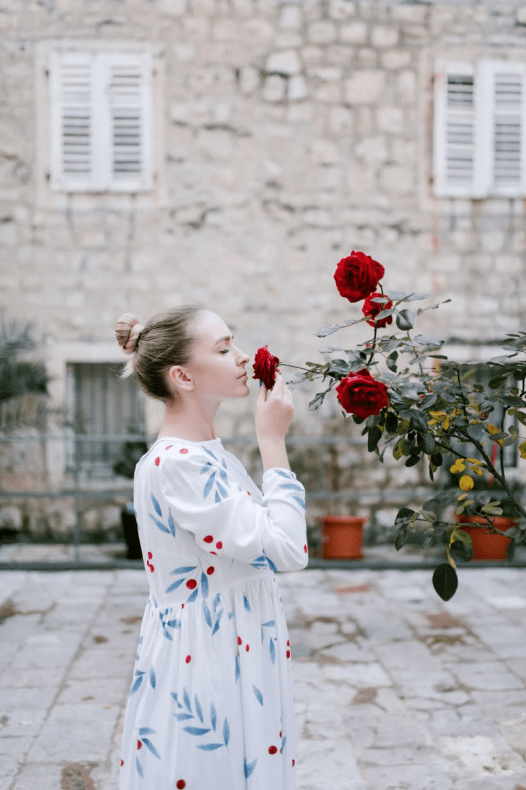 natural living, woman in white and floral dress, smelling a red rose that is growing on a bush