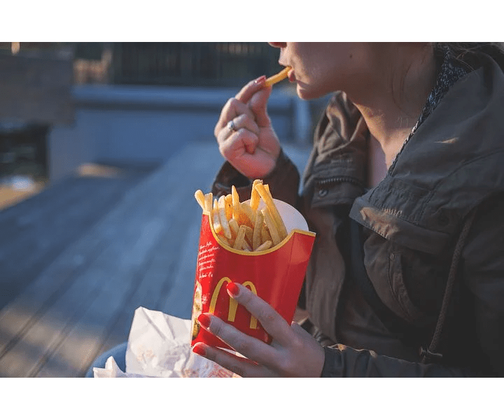 high cholesterol, person eating mcdonald's fries