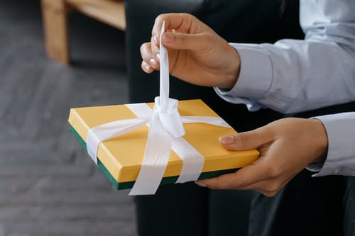 Father's Day gifts, hand opening white ribbon on yellow gift