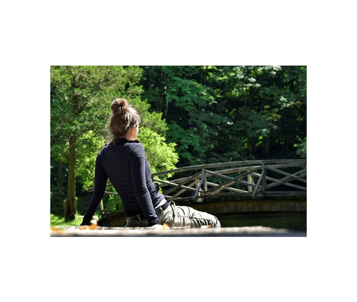 spending time alone, woman with hair in bun sitting on dock, leaning back