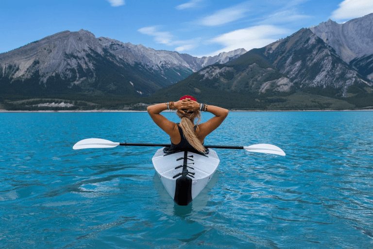 kayaking, woman with hands on head, sitting in kayak, mountains