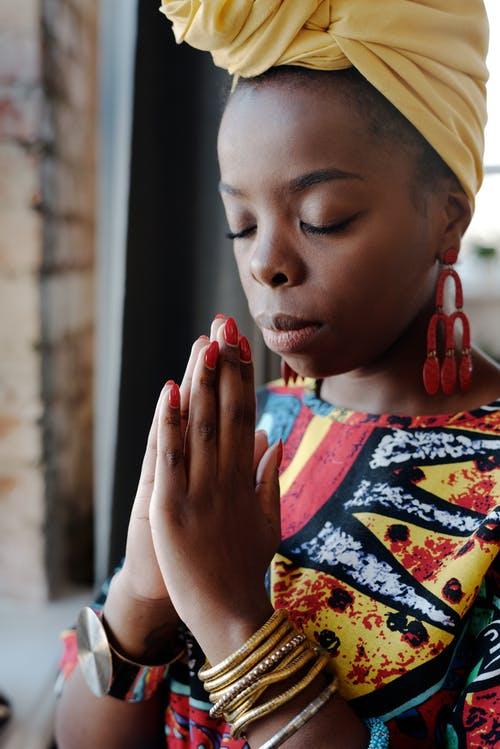 black woman, yellow head turban, eyes closed, hands folded in prayer