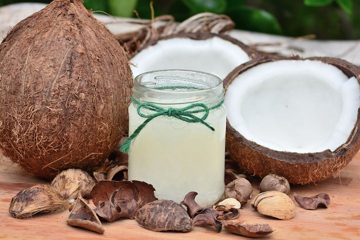 coconut oil, whole coconut, halved coconut, glass jar with green twine bow filled with oil