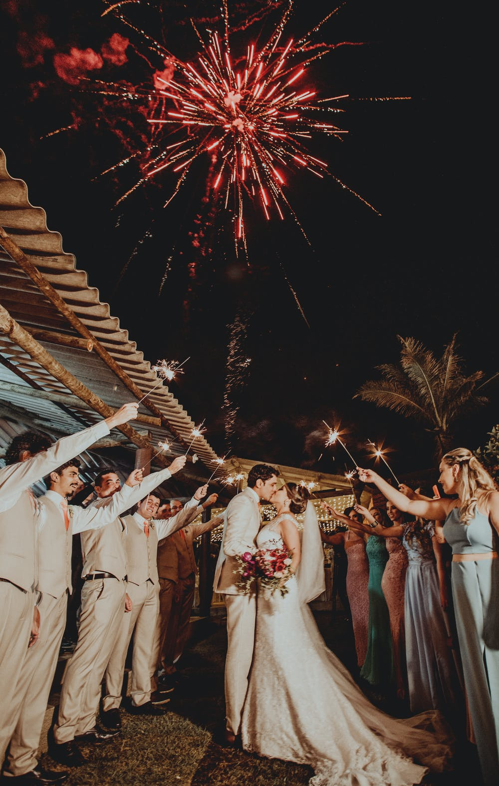 wedding customs, line of men and women holding sparklers over bride and groom