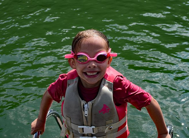 ocean safety tips, child wearing goggles and life jacket in water