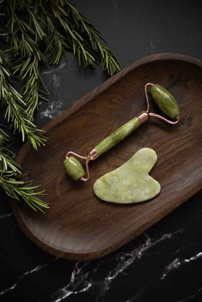 gua sha, jade stone and roller on small brown tray, greenery nearby