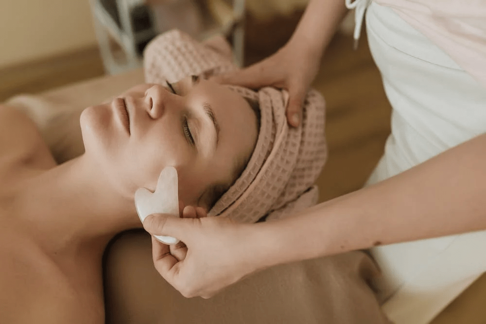 gua sha, woman lying down, towel on head, hands of masseuse shown using stone on face
